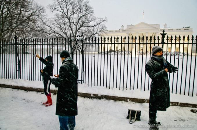 Tourists out in front of the White House with snow in the evening