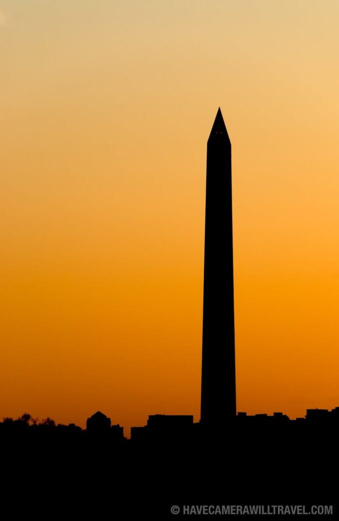 Washington Monument at dusk against golden glow of sunset